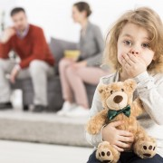 Worried boy with teddy bear, holding hand on her mouth, in the background man and woman sitting on sofa